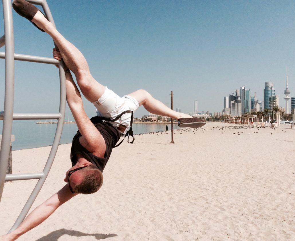 jongeman op et strand van kuweit aan het paaldansen aan een speeltoestel. Met op de achtergrond de skyline van kuweit