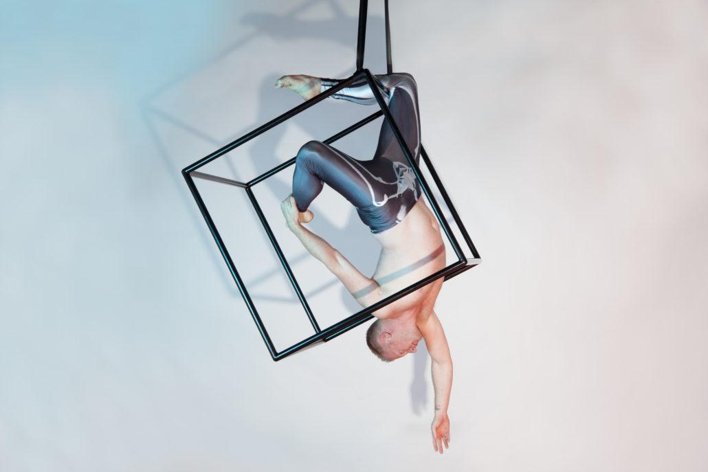luchtacrobaat in een aerial cube hangend aan 1 been