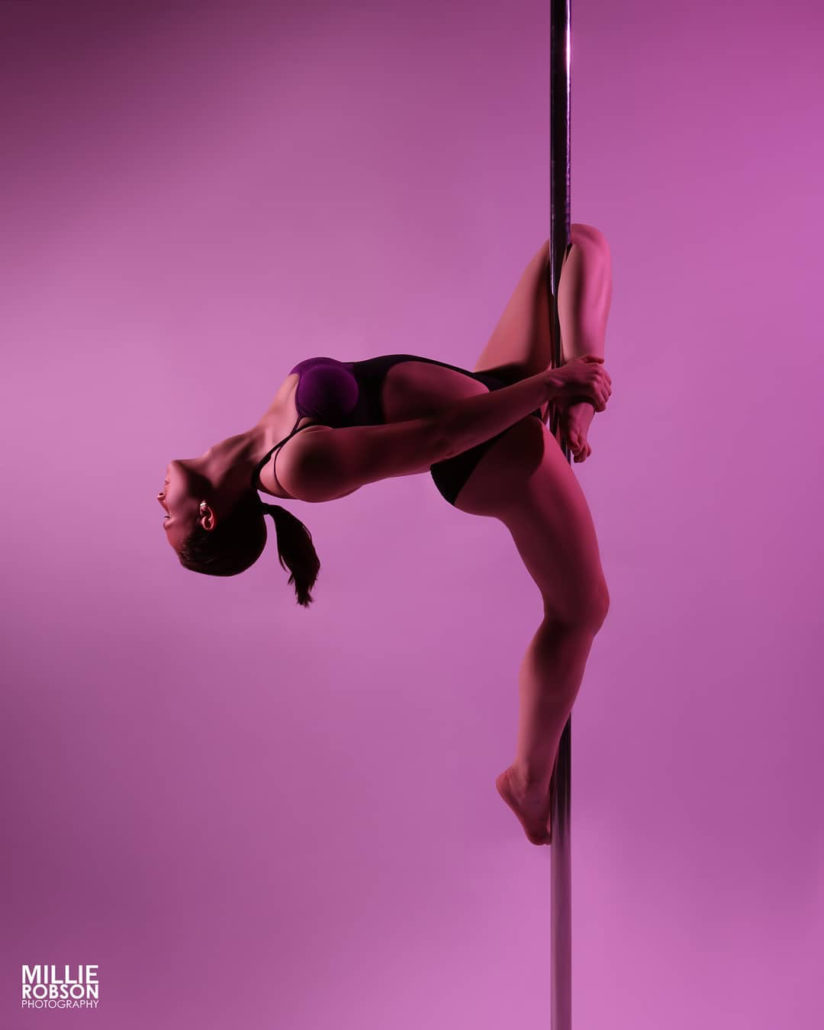 paaldanseres op purperen achtergrond. hangend aan haar linkerbeen met een buiging in de rug naar achter steunend op haar rechterbeen onderaan tegen de paal