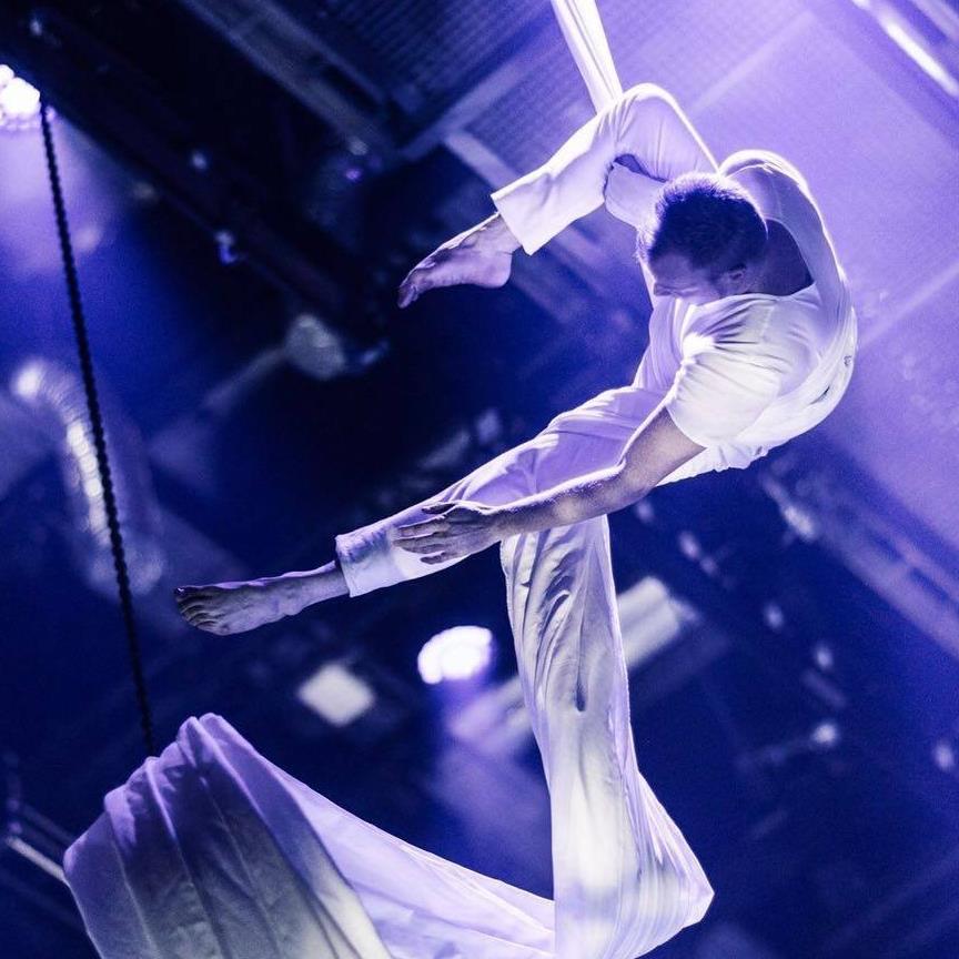 man hangt in de lucht met witte doen als een circusacrobaat.hij wikkelt een doek rond zijn been tijdens het klimmen