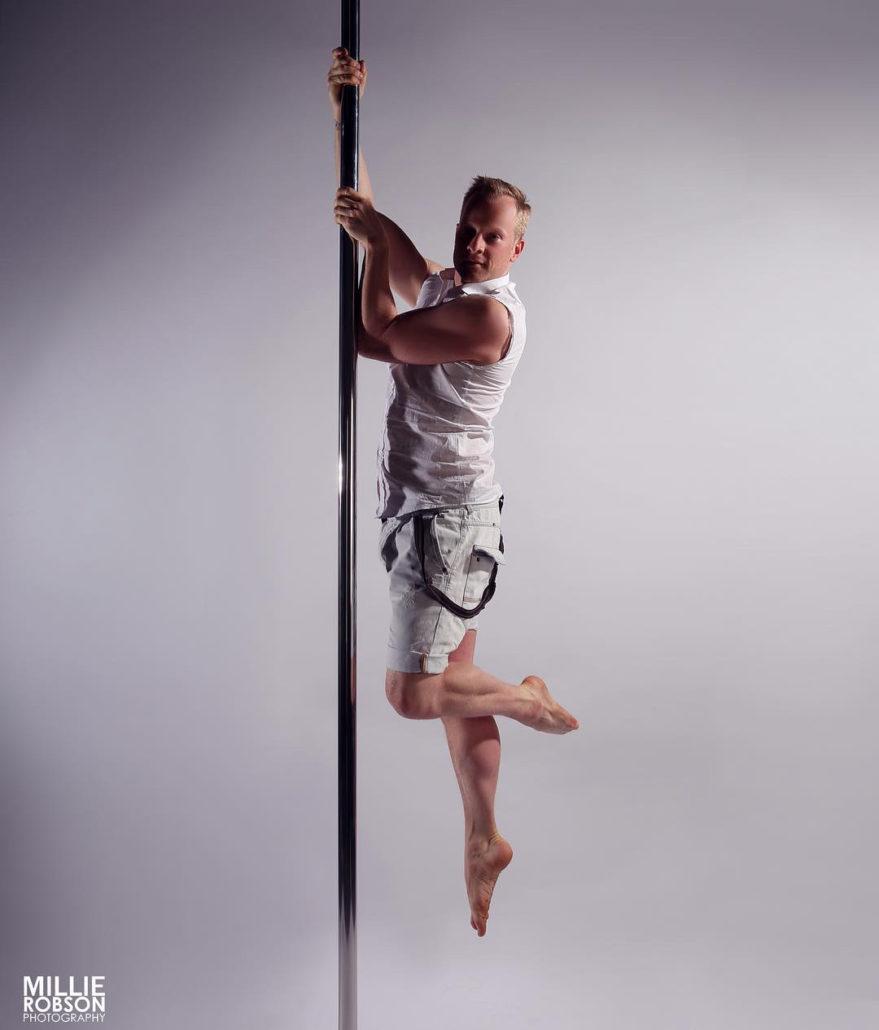 man hangt als een recht potlood langs de paal, met een jeansshit en wit mouwloos hemd