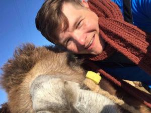 knappe man met een bruin rode sjaal knuffelt een kameel.