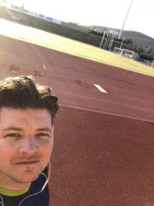 Sam in de zon met op de achterkant een atletiekbaan